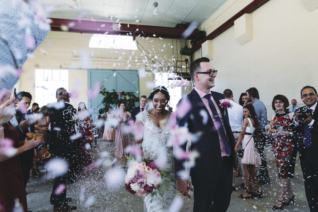 bride and groom exit ceremony with confetti